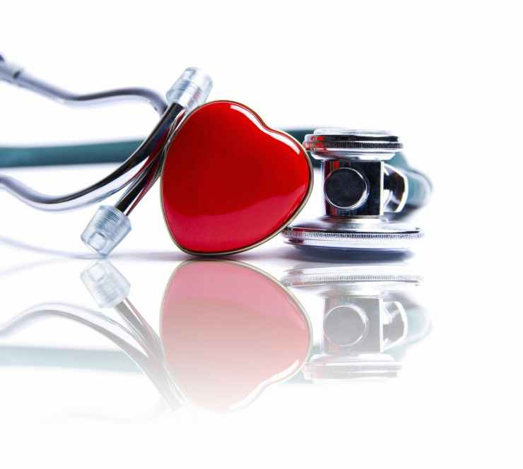A picture of a stethoscope with a shiny red heart attached to it.