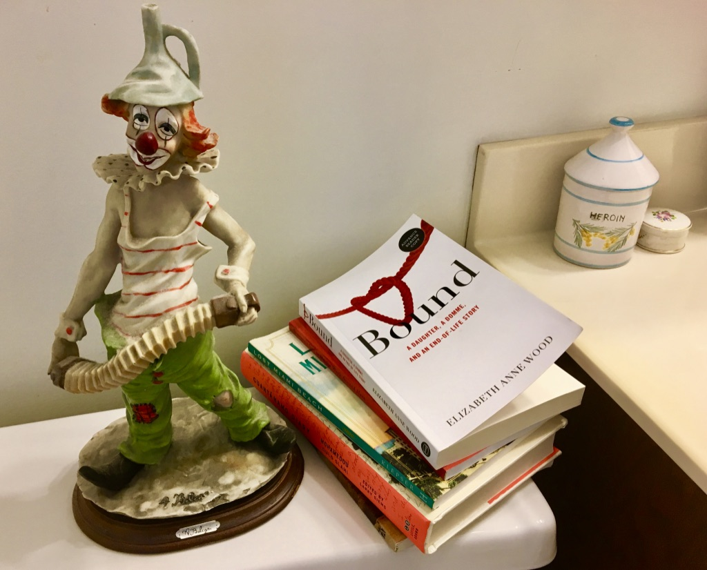 a stack of books on the tank of a toilet. The top book is Bound: A Daughter, a Domme, and an End-of-Life story. Beside the books is a ceramic clown.